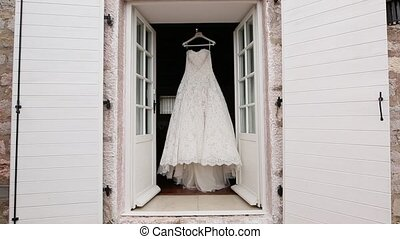 The bride's dress hangs on the cornice on the window.
