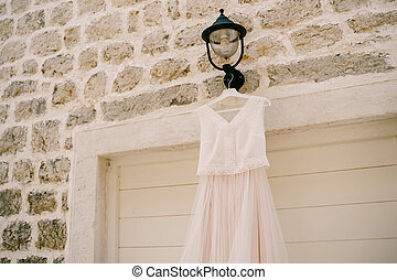 The bride's dress on the background of a stone wall on a black street lamp.