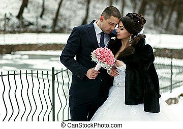 The brides embrace near frozen lake