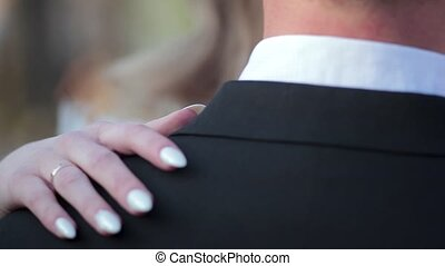 The bride's hands gently embrace the groom by the shoulders and stroke him