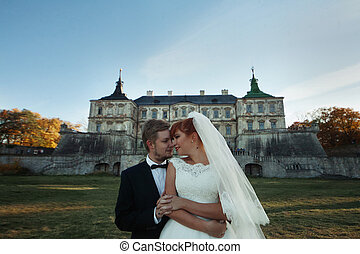 The brides stand near castle