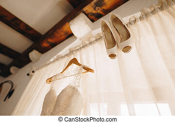 The bride's wedding dress on a hanger and white shoes on the background of closed curtains on the cornice.