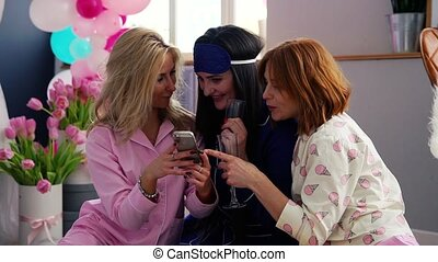 The bridesmaids sitting in a circle bumping glasses with...
