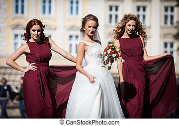 The bridesmaids with bride stand in the center of town