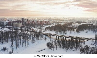 The bridge across the river winter. Span over the city with a bird. 4K Aerial. Over frozen city river and bridge in sunrise, sunset