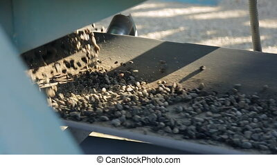 The broken particles of crushed stone and sand moved...