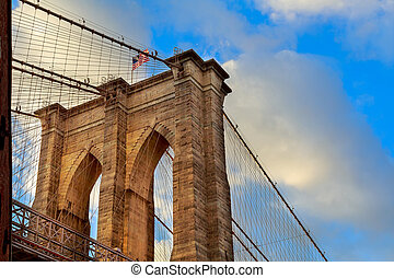 The Brooklyn Bridge, New York. Architectural detail at summer sunset.