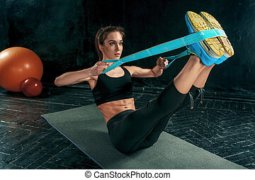 The brunette athletic woman exercising with rubber tape on...