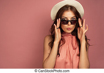 The brunette is standing on a pink background in a straw hat, looking into the camera while lowering her sunglasses.