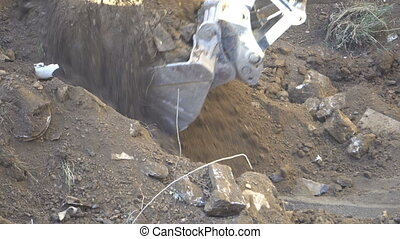 the bucket of the excavator digs the ground and carries it...