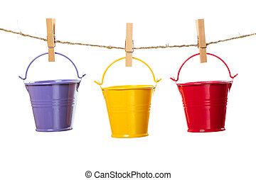 Three buckets hanging on the rope isolated on white background