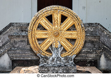 The Buddhists? Symbol, golden wheel with base of deer look back in old Pa Dang temple, Chiang Mai, Thailand (forgotten temple)