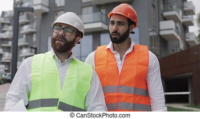 The builder and architect man are discussing the construction plan of the modern business center walking near construction site. They checks the work with architectural drafting.