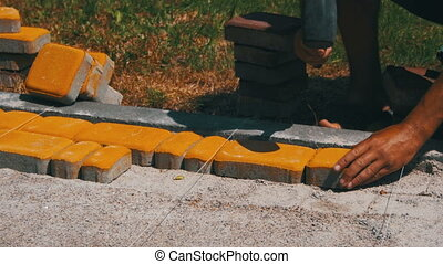 The Builder is Laying Paving Stones - The builder is laying...