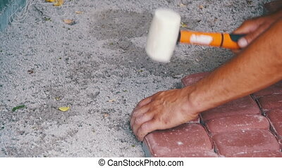 The Builder is Laying Paving Stones. Slow Motion - The...