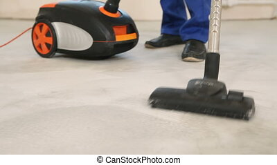 The builder vacuums the floor of dust