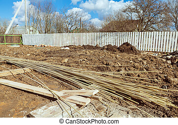 The building is under construction with new foundation after concrete pouring and making reinforcement metal framework and construction materials for that