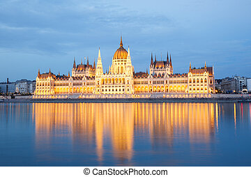 The building of Parliament with reflection in the river in Budapest at sunset