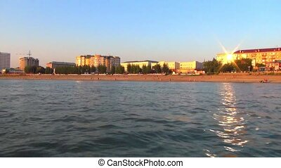 The building of the city river station of the Siberian city, Russia, shooting at the side of the boat at sunset