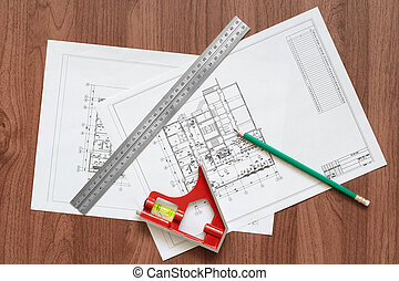 The building plan and tools on a wooden table.