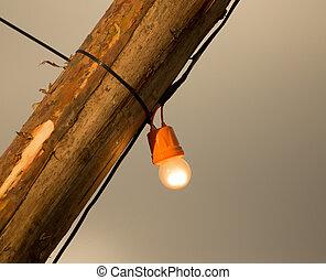The bulb burns on a wooden pole