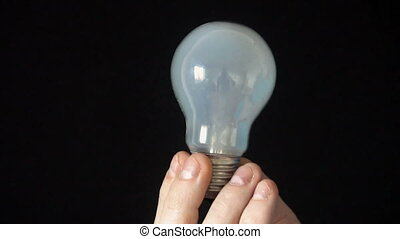 the bulb lights up in the hands of a young man,Black background