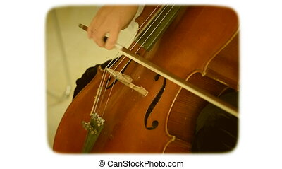 The bow moves along the strings of a double bass. Styling under an 8mm film is a retro style movie. in the style of the styling of the 1970s. White-black frame with interference on the video.