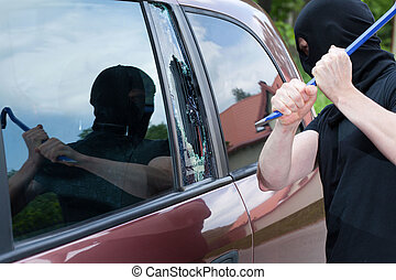 The burglar smash the glass of the car - The burglar smash...