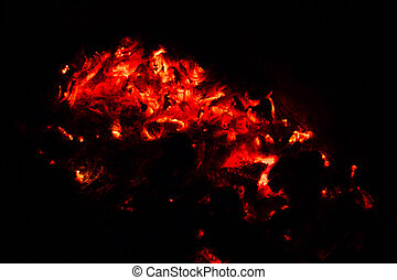 The burning coals of a BBQ in the dark