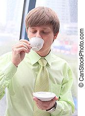 The businessman drinks coffee