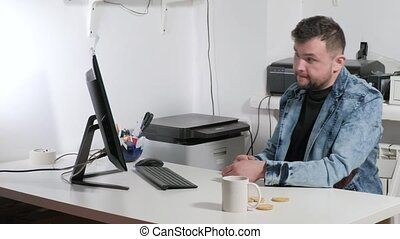 The businessman emotionally conducts a dialogue. In the office, sitting at the computer 4k