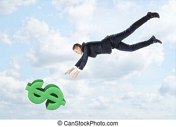 The businessman flying down to the big dollar sign with his hands outstreched on the background of the blue sky.