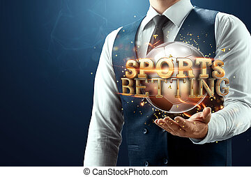 The businessman has a gold inscription sports betting on his palm. Concept for gambling, sports, online betting. Mixed environment