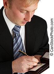The businessman in a black suit signs a paper.