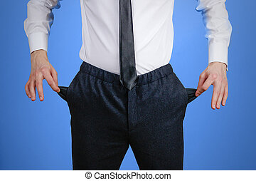 The businessman in a white shirt and black trousers shows his empty pockets. Isolated on blue background
