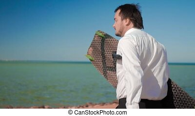 The businessman in suit runs to the sea with a kitesurf board