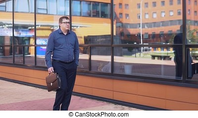 the businessman is walking near the business center and talking on the phone. HD