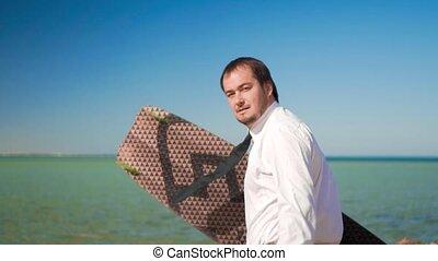 The businessman runs to the sea with a kitesurf board -...