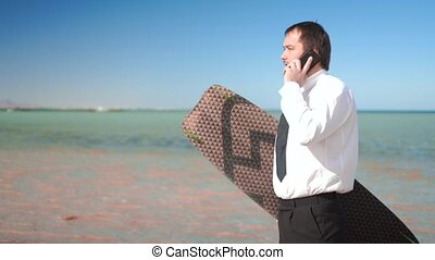 The businessman stands on the seashore and keeps the board...