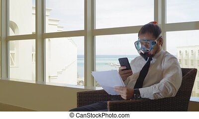 The businessman working in the lobby in the mask of...