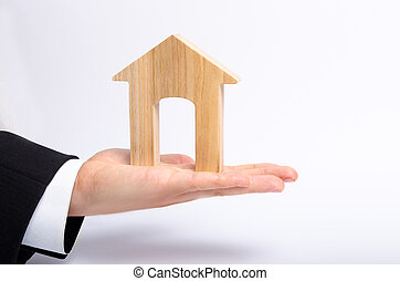 The businessman's hand stretches a wooden house with a large doorway. The concept of commercial real estate, the purchase and sale of residential buildings, apartments. Rental of property.