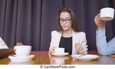 The businesswoman in the glasses drinks coffee with her partners in the luxuty cafe.