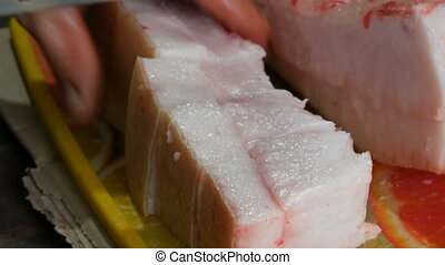 The butcher cuts large piece of pork meat and fat - The...