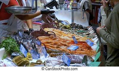 The buyer gives money to the seller for purchased Sea food in La Boqueria. Barcelona. Spain