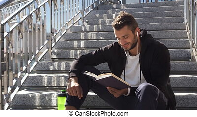 The calm guy is reading a book sitting on the steps