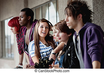 The camera focuses on the attractive young smiling punk girl as her friends take no notice.
