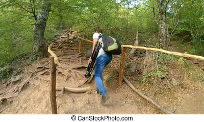 The camera watches as a man climbs the mountain path. - The...
