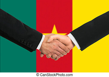 The Cameroonian flag and business handshake