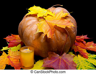 The candle burns before pumpkin with a maple leaf