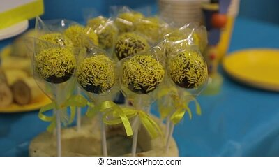 Lollipop candys on stick chocolate children birthday party yellow blue color candy bar